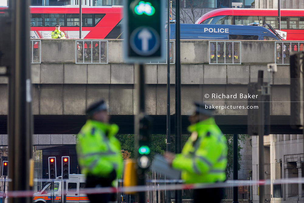 The morning after the terrorist attack at Fishmongers Hall on London Bridge, in which Usman Khan (a convicted, freed terrorist) killed 2 during a knife a attack, then subsequently tackled by passers-by and shot by armed police - officers guard Upper Thames Street that is still cordoned off, on 30th November 2019, in London, England.