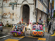 05 OCTOBER 2014 - GEORGE TOWN, PENANG, MALAYSIA: Malaysian Muslim women watch a Hindu procession honoring Durga in George Town during the Navratri procession. Navratri is a festival dedicated to the worship of the Hindu deity Durga, the most popular incarnation of Devi and one of the main forms of the Goddess Shakti in the Hindu pantheon. The word Navaratri means 'nine nights' in Sanskrit, nava meaning nine and ratri meaning nights. During these nine nights and ten days, nine forms of Shakti/Devi are worshiped.   PHOTO BY JACK KURTZ
