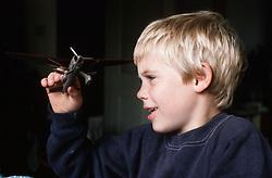 Young boy playing with model aeroplane,