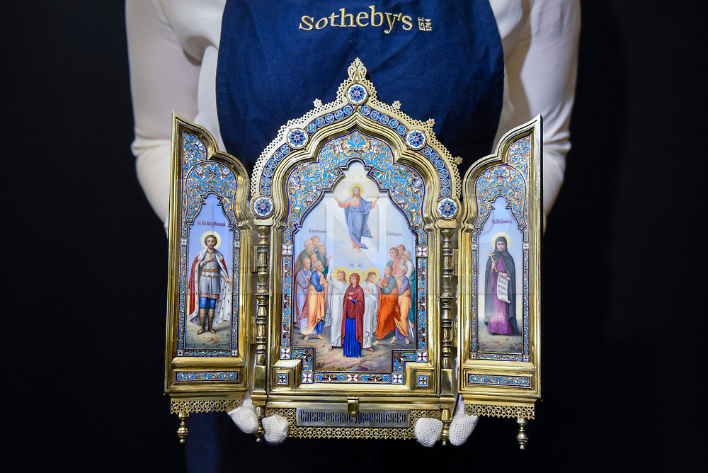 """© Licensed to London News Pictures. 22/11/2019. LONDON, UK. A technician presents """"A silver-gilt, cloisonné and pictorial enamel triptych icon"""", 1899-1908, by Khlebnikov, Moscow (Est. GBP100-150k) at the preview for the upcoming sales of Russian artworks at Sotheby's New Bond Street.  The Russian Pictures and Works of Art, Fabergé and Icons sales take place on 26 November.  Photo credit: Stephen Chung/LNP"""