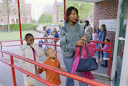 Single mother taking young daughter and son to primary school,