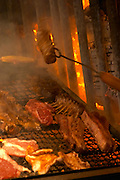 The gigantic huge charcoal grill with pieces of meat being cooked, the chef in white with a grilling fork turning a piece of meat, in the restaurant El Palenque, the sword fish swordfish, in the Mercado del Puerto, the market in the port harbour harbor where many people go and eat and shop on weekends Montevideo, Uruguay, South America