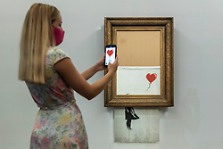 """© Licensed to London News Pictures. 03/09/2021. LONDON, UK.  **UNDER EMBARGO UNTIL FRIDAY 3 SEPTEMBER 2021, 12PM BST** A staff member photographs """"Love Is in the Bin"""" by Banksy at a preview at Sotheby's.  The painting, originally known as """"Girl with Balloon"""", was famously shredded by the artist in Sotheby's London auction room in 2018 after being sold for £1,042,000.  The resulting artwork was later renamed """"Love Is in the Bin"""" and will be offered for sale in Sotheby's contemporary art evening auction on October 14 with an estimate of £4-6 million.  Photo credit: Stephen Chung/LNP"""