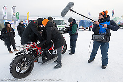 A media team surrounds Mikhail Mikhin on the Moscow Polytechnic University electric motorcycle that built for the Baikal Mile Ice Speed Festival. Maksimiha, Siberia, Russia. Thursday, February 27, 2020. Photography ©2020 Michael Lichter.