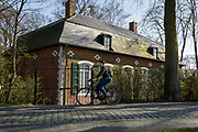 A woman cycles past the gamekeeper's house at the entrance of the privately-owned de Merode Castle, on 25th March, in Everberg, Belgium. The gamekeeper's house lies alongside the cobbled Princes Lane (Prinsendreef) in Everberg and was built around 1770. The house was more familiar as the New Hostel (Nieuwe herbergh). This house was rented. Art historians described it as an 18th-century house in provincial regency style. In the end of the 19th century the house became the gamekeeper's house of de Merode Castle. The latter is the owner of the house as well. The gamekeeper's house is known in Everberg as the previous house of 'Jef van Vinus' or Jozef Meersman, who was the actual gamekeeper. <br /> <br /> <br /> <br /> on 25th March, in Everberg, Belgium.
