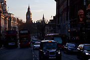 Looking down Whitehall to the Houses of Parliament. London taxis and buses in the evening light.