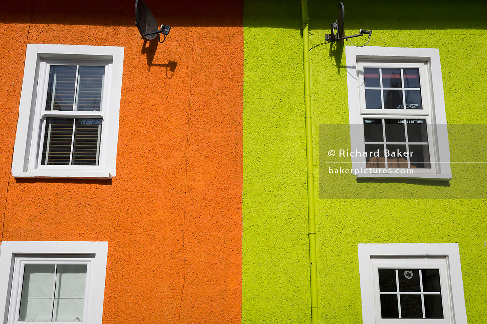 Orange and lime green neighbouring houses, on 12th September 2018, in Aberdovey, Gwynedd, Wales.