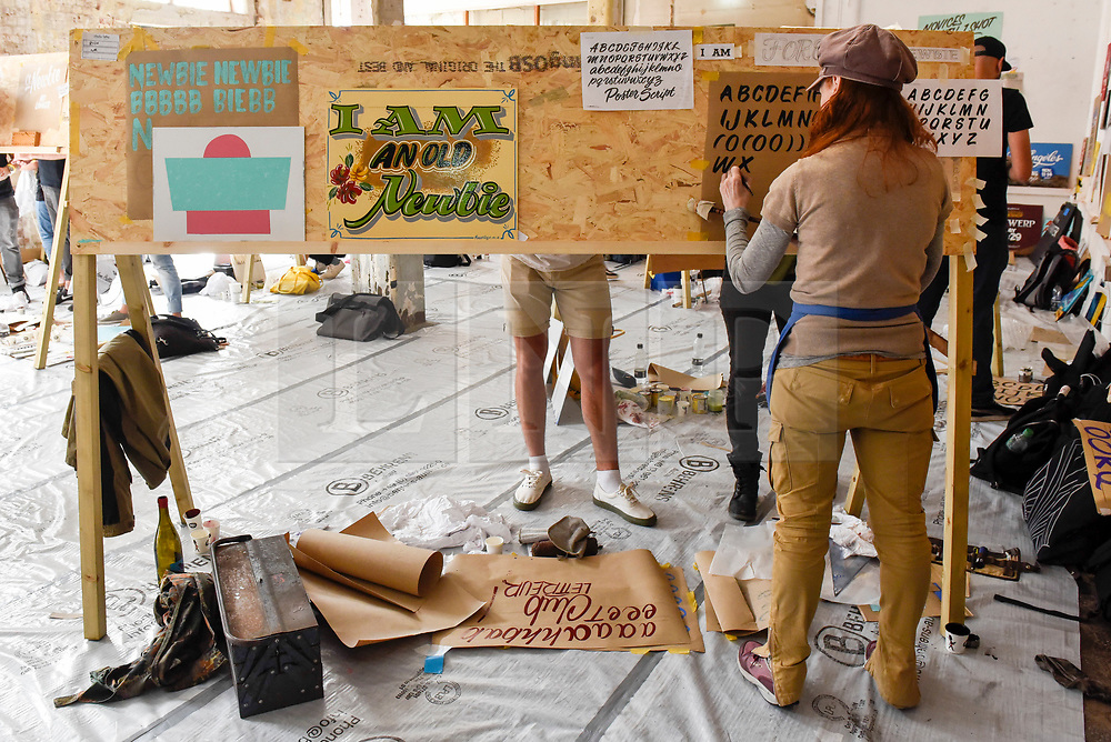"""© Licensed to London News Pictures. 17/08/2018. LONDON, UK. Novice sign writers practice at """"Letterheads 2018: London Calling"""", an international gathering of professional sign writers and lettering artists from over 30 countries.  The event is taking place at the Bargehouse, Oxo Tower Wharf in central London untikl 19 August.  Photo credit: Stephen Chung/LNP"""