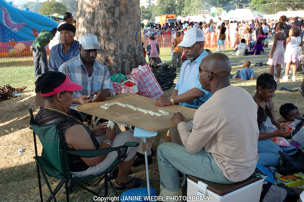 West Indian men playing dominos in the park on a summer day.