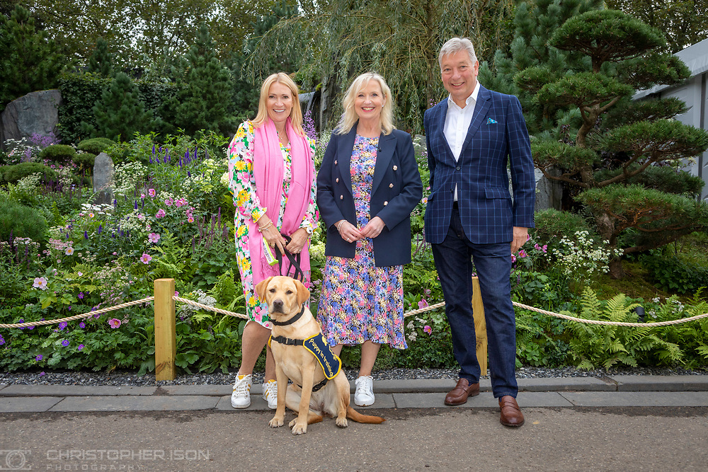 Puppy walkers Steve and Mel with puppy Flash in the Artisan Garden at RHS Chelsea created this year in celebration of 90 years of guide dog partnerships in Britain. Chelsea is 18 weeks-old and named to celebrate the event.<br /> Picture date: Monday September 20, 2021.<br /> Photograph by Christopher Ison ©<br /> 07544044177<br /> chris@christopherison.com<br /> www.christopherison.com