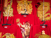 """31 JANUARY 2016 - BANGKOK, THAILAND: Chinese New Year tee shirts, decorated with monkey graphics, at a stand on Yaowarat Road in Bangkok's Chinatown. Chinese New Year, also called Lunar New Year or Tet (in Vietnamese communities) starts Monday February 8. The coming year will be the """"Year of the Monkey."""" Thailand has the largest overseas Chinese population in the world; about 14 percent of Thais are of Chinese ancestry and some Chinese holidays, especially Chinese New Year, are widely celebrated in Thailand.           PHOTO BY JACK KURTZ"""
