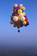 John Ninomiya, a cluster balloonist is attached to some 82 balloons using only