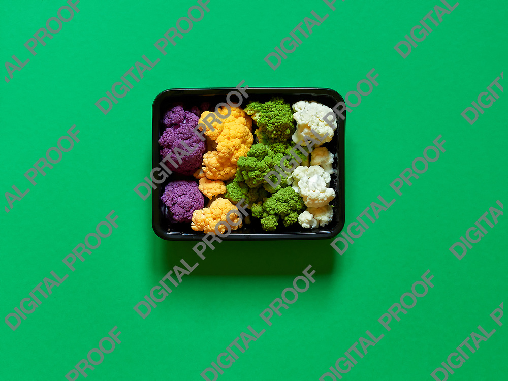 Set of seasonal and colorful cauliflower violet, yellow, green and white boxed in a plastic recipient over a green background