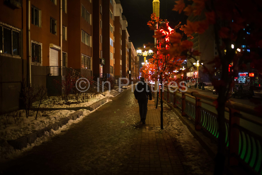 A man walks down a street at night in the Erdaojiang district in Tonghua, Jilin province, China, on Wednesday, Jan. 6, 2016. The citys once-vaunted state-run steel mills have slipped inexorably into decline, weighed down by slumping global markets, a changing economy, and the burden of costs and responsibilities to the people of the town they fostered. Previous attempts to privatise the enterprise have met with stiff resistance, one such attempt resulted the mob lynching and death of a private businessman who wanted to invest and streamline the operation.