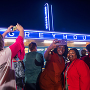 Kelsea Merriweather, center left, and Angela Calhoun take a photo of themselves and the neon sign on the old Greyhound station as it is lit for the first time in 60 years in downtown Jackson, Tennessee. The building is being remodeled for a new business project. Nathan Lambrecht/Journal Communications