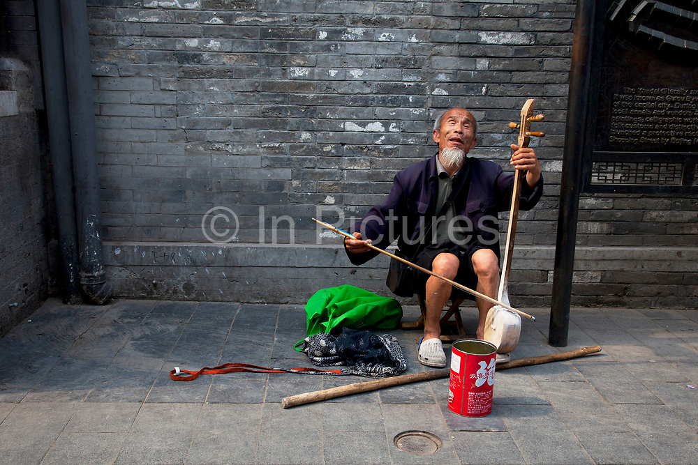 Blind man busking on Yandaixiejie Street (meaning Tobacco Pipe Lane) in Beijing, China. Located near to Houhai in downtown Beijing, Yandai Xiejie Street is a Hutong which attracts many tourists at day and night to it's souvenir shops and towards the bar area it leads to.
