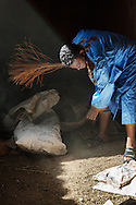 A traditional dressed Moroccan man cleans a dusty room in a Kasbah.