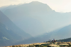 Couple of mountainbikers looking at view and sitting on bench in alpine landscape, Zillertal, Tyrol, Austria