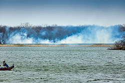 A prescribed or controlled burn along the earthen dam of Evergreen Lake at Comlara Park.  A controlled or prescribed burn, also known as hazard reduction burning, backfire, swailing, or a burn-off, is a fire set intentionally for purposes of forest management, farming, or prairie restoration.  Several of these are performed annually at the park.