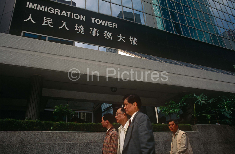 Hong Kong Chinese walk beneath the ImmigrationTower in Central, a year before the handover of sovereignty from Britain to China, on 29th March 1996, in Hong Kong, then a British colony but latterly, China.