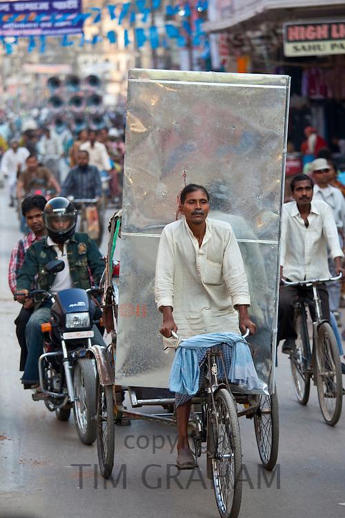 Indian man driving rickshaw with heavy load in street scene in city of Varanasi, Benares, Northern India