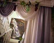 The decorative curtains with fake grapes, and waterfall mural wallpaper, of a newly decorated home in the village of Sintesti, in Romania, early August 2006. The Kalderari roma of Sintesti are by tradition metal workers, originally making alcohol stills, pots and pans, but now dealing in scrap metal. The large profits from their business have enabled them to build large houses in the village of Sintesti, 20km from Bucharest, and to invest in fast, Western brand name cars such as BMW's, Mercedes and Porsche.