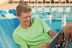 Young male swimming pool holding tablet computer