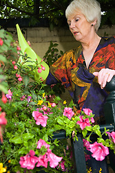 Older woman watering her plants outside,