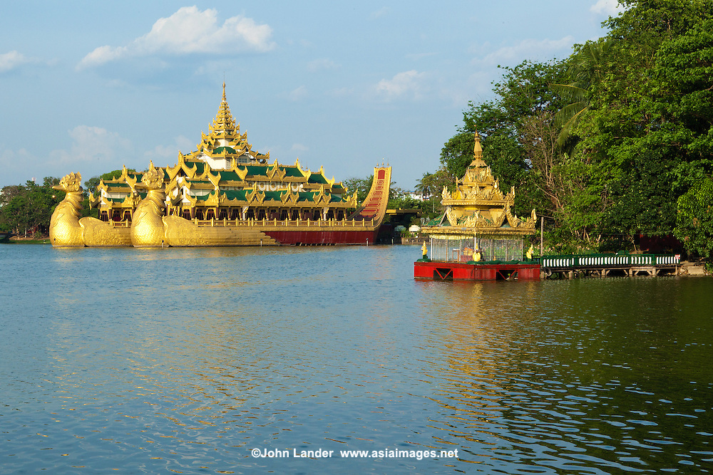"""Kandawgyi Lake literally """"great royal lake"""" was once known as Royal Lake) -  one of two major lakes in Yangon.  Located east of the Shwedagon Pagoda, the lake is artificial; water from Inya Lake is channelled through a series of pipes to Kandawgyi Lake. It was created to provide a clean water supply to the city during the British colonial administration..The 150-acre lake is surrounded by Kandawgyi Nature Park and Yangon Zoological Gardens, which consists of a zoo, aquarium and amusement park"""