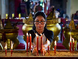 September 4, 2017 - Bangkok, Bangkok, Thailand - A woman lights prayer candles at Chaomae Thapthim Shrine before a food distribution event at the shrine. About 1,000 people came to the shrine for the annual food distribution. Staples, like rice and cooking oil, are donated to the shrine throughout the year and donated to poor people from the communities around the shrine. Food distributions like this are a tradition at Chinese shrines in Bangkok and a common way of making merit for the people who donate the staples. (Credit Image: © Sean Edison via ZUMA Wire)