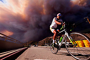 A man rides on along the Pacific Coast Highway as the  heavy smoke rises over the the Santa Monica Mountains during the Woolsey fire in Malibu, Calif., Friday, Nov. 9, 2018.  The Woolsey Fire was a destructive wildfire that burned in Los Angeles and Ventura Counties of the U.S. state of California. The fire ignited on November 8, 2018 and burned 96,949 acres of land.