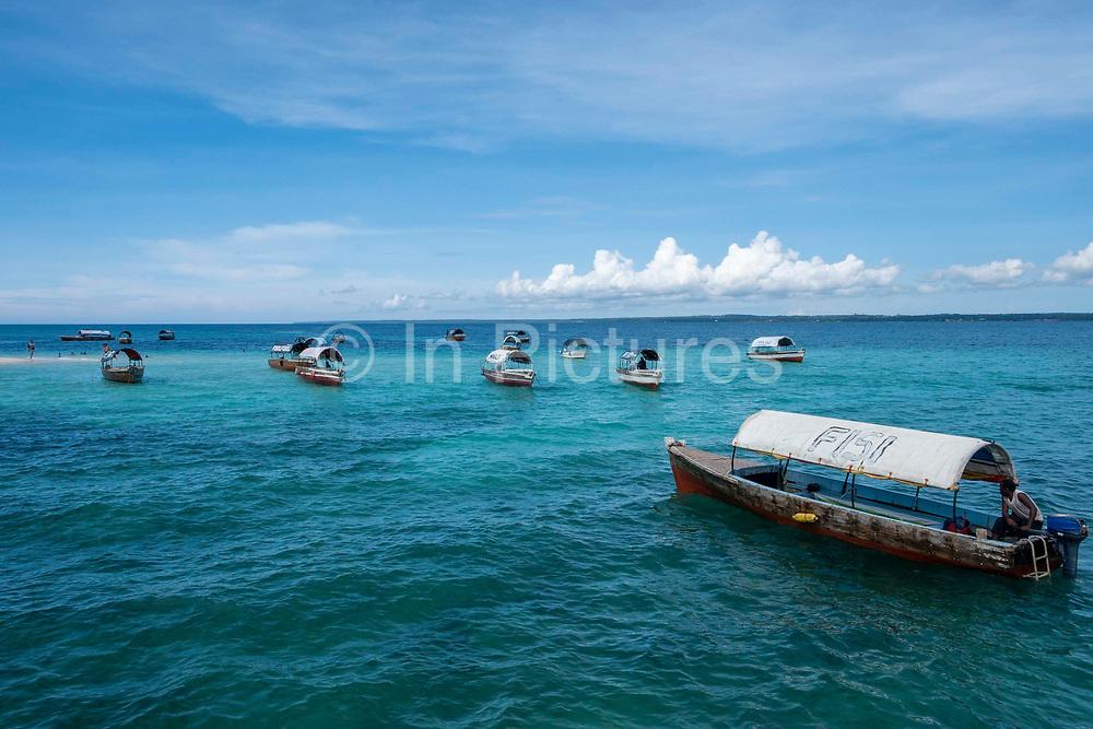 Tourist taxi boats wait in the shallow waters off Changuu island, also known as prison island,  Zanzibar, Tanzania.  Tourists visit prison Island on a daily basis from Stone Town, Zanzibar.