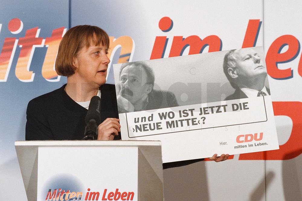 """07.01.1999, Deutschland/Bonn:<br /> Angela Merkel, CDU Generalsekretärin, mit einem Plakat """" und wo ist jetzt die neue Mitte?"""", während einer Pressekonferenz, Konrad-Adenauer-Haus, Bonn<br /> IMAGE: 19990107-01/01-18<br /> KEYWORDS: Plakat, bill, Werbung, promotion"""