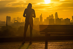 Primrose Hill, London, October 28th 2016.A woman takes a break from her run on Primrose Hill as the sun rises over London's skyline.