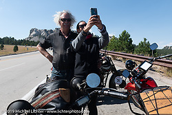 Land-speed record holder Jody Perewitz stops to take a selfie with Doug Feinod during the Motorcycle Cannonball coast to coast vintage run. Stage 9 (294 miles) from Pierre to Sturgis, SD. Sunday September 16, 2018. Photography ©2018 Michael Lichter.