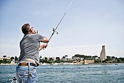 Un pescatore al Porto di Brindisi mentre lancia l'amo con l'esca in mare con allo sfondo il Monumento al Marinaio in viale Duca degli Abbruzzi. 29/05/2010 PH Gabriele Spedicato
