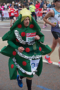 A male runner dressed as a Christmas tree on Birdcage Walk during The Virgin London Marathon on 28th April 2019 in London in the United Kingdom. Now in it's 39th year, the London Marathon is a large sporting event with over 40,000 runners expected to take part.