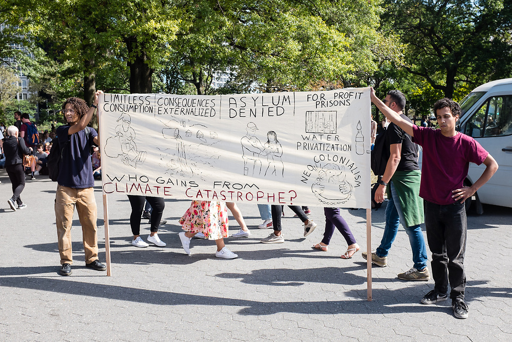"20 September 2019 - New York, NY.  Thousands of students as well as adults gathered in New York for the Global Climate Strike, meeting in Foley Square near the Federal Government buildings and New York's City Hall, and marching downtown to Battery Park, where Swedish climate activist and spokesperson Greta Thunberg addressed the crowd. A large banner describes a number of climate issues and poses the question ""who gains from climate catastrophe?"""
