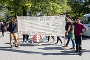"""20 September 2019 - New York, NY.  Thousands of students as well as adults gathered in New York for the Global Climate Strike, meeting in Foley Square near the Federal Government buildings and New York's City Hall, and marching downtown to Battery Park, where Swedish climate activist and spokesperson Greta Thunberg addressed the crowd. A large banner describes a number of climate issues and poses the question """"who gains from climate catastrophe?"""""""