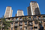 Old traditional tenement housing in the shadow of new modern high rise apartment blocks at Mahalaxmi in Mumbai, India