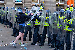 Glasgow, Scotland, UK. 15 May 202. Rangers football supporters  celebrating 55th league victory are cleared from George Square by police in riot gear on Saturday evening. In very violent scenes police were pelted with bottles and items from a nearby construction site as police pushed the supporters into the south west corner of the square. Pic; man approaches police and is forced back . Iain Masterton/Alamy Live News.