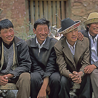 CHINA, TIBET. Young Tibetan village men admire passing girls at a small-town festival.