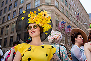 New York, NY - April 16, 2017. A woman in a bright yellow dress wears a black straw hat decorated with yellow flowers under the brim at New York's annual Easter Bonnet Parade and Festival on Fifth Avenue.