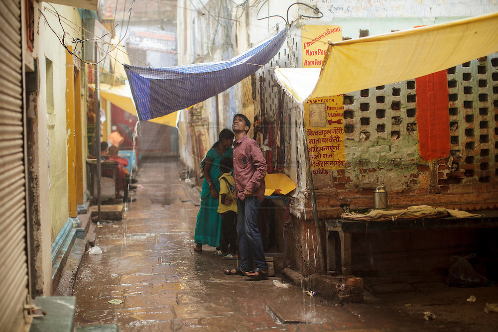 Young family sheltering from the rain in a alley at Varanasi in India.