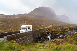 Bridge and motorhome in the rain at start of climb into Bealach na Ba pass on Applecross Peninsula  the North Coast 500 scenic driving route in northern Scotland, UK