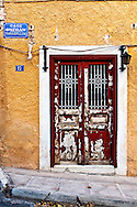 A red door in a yellow wall in Athens, Greece