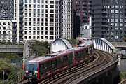 A Docklands Light Railway (DLR) train passes over a bridge beneath high-rise residential properties at Canning Town in Newham, on 11th August 2021, in London, England.