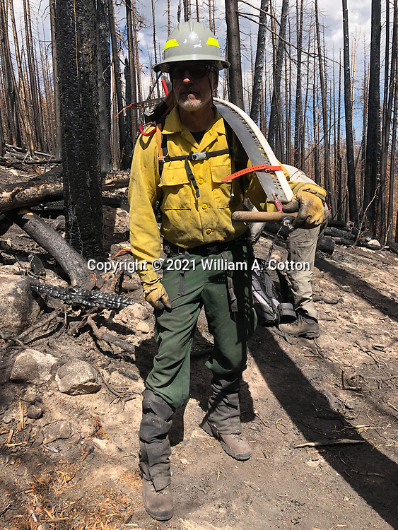 Diamond Peaks Ski Patrol member Bill Cotton carries a crosscut saw to clear trees on the Blue Lake Trail, June 8, 2021, the spring after the Cameron Peak Fire.