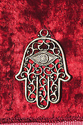 decorated silver Hamsa on red velvet background
