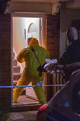© Licensed to London News Pictures. 27/01/2020. Slough, UK. A forensic investigator steps into a house to gather evidence after Thames Valley Police responded to an incident in Slough, unconfirmed reports of a 'stabbing' and 'acid attack' centred around the dwelling on a quiet street in the area. Photo credit: Peter Manning/LNP